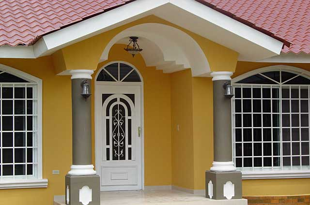 Example of a modern townhouse entrance with a mustard yellow tone on the walls, a dark grey on the columns, white window & door frames and white ceiling elements in combination with the regular red roof tiles