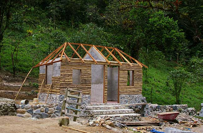 Photo of a little mountain cabin with natural stone foundations and wood and cement wall elements