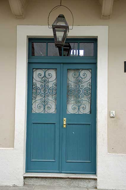 Photo Example of a traditional old door in light blue with glass panels and a decorative metal security cover.