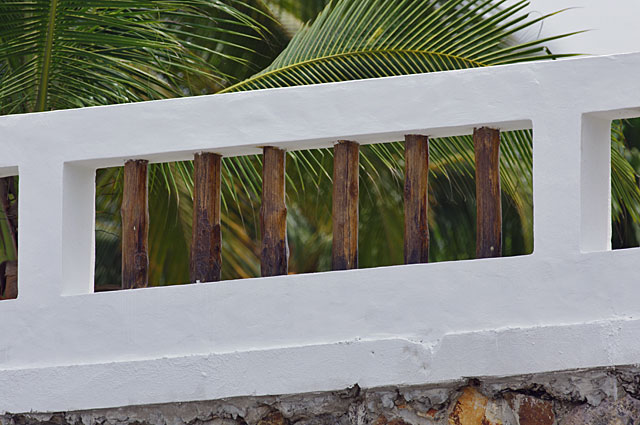 Photo Example of a good looking beach house fence made of cement frames painted in white and natural wood