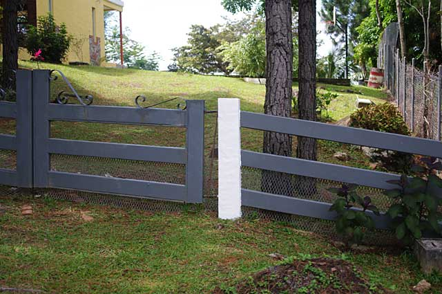 Photo Example of a simple fence around a mountain home with white pillars and grey metal bars