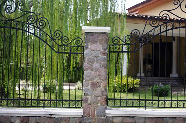Photo Example of a decorative fence around a town house with natural stone pillars and black metal bars