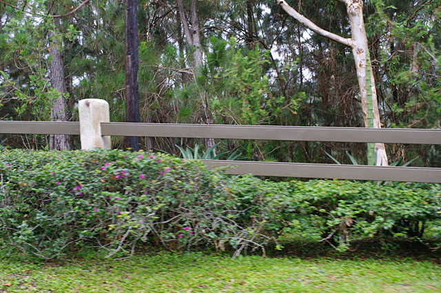 Photo Example of a simple fence around a mountain property with beige stone pillars and olive green painted bars