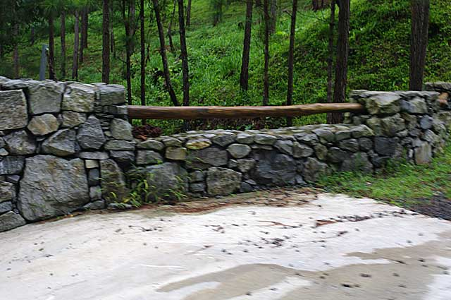 Photo Example of a simple stone wall around a mountain property with a wood bar