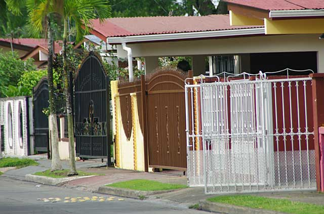 A series of gates on some town houses with different colors and shapes all made of metal