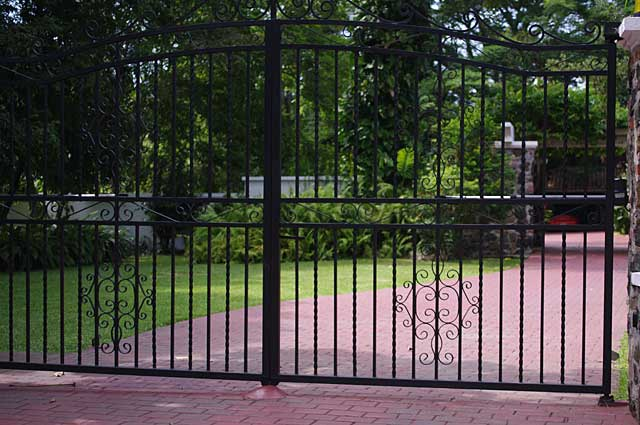 Photo example of simple but elegant black metal gate in front of colonial house