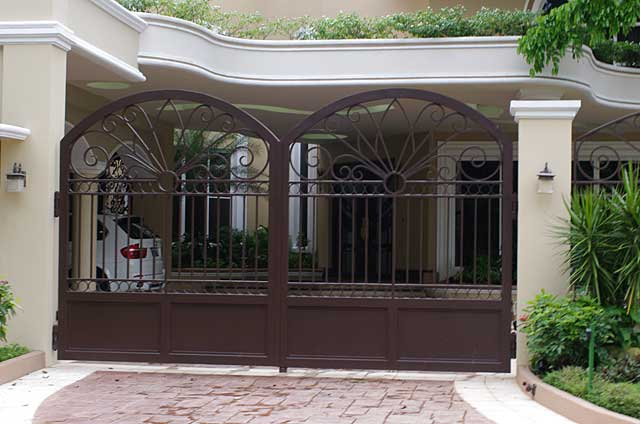 Photo of a luxurious heavy brown or dark bronze colored metal gate in front of a city condo