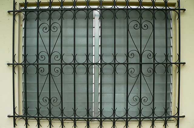 Picture of simple but decorative black metal window security bars
