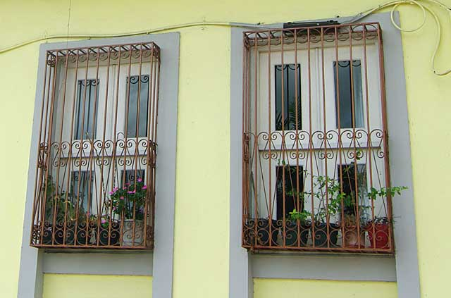 Image some simple but decorative metal security bars covering the windows of this house. These metal bars leave some room between the window and the bars to allow to place there some decorative flower pot