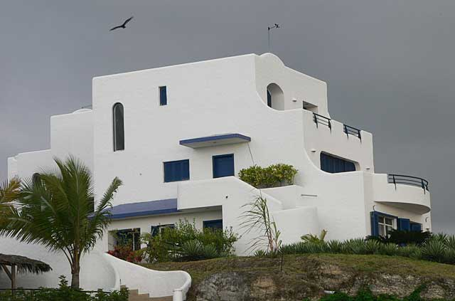 Photo example of a modern apartment complex painted in white in combination with deep blue, at a top location, overlooking the Pacific Ocean