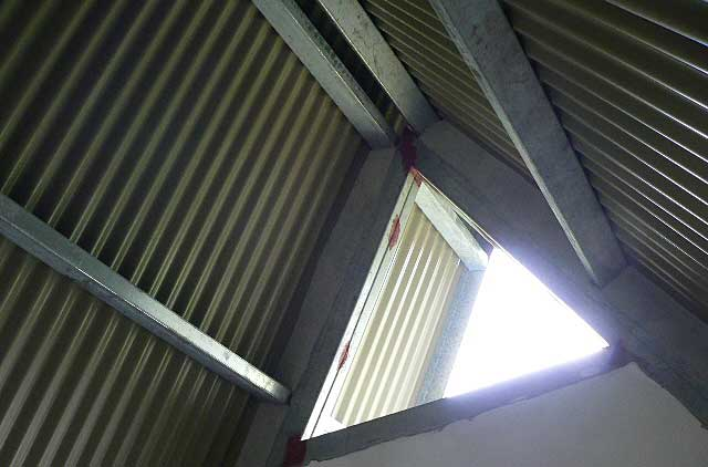 Example photo of the inside of a house under construction with a simple zinc roofing