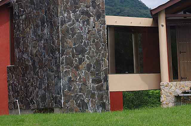 Photo example of a wall on a country home covered with dark grey almost black stone plates