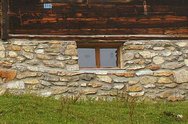 Photo example of a wall on a Swiss alpine mountain house built with local natural beige stone plates