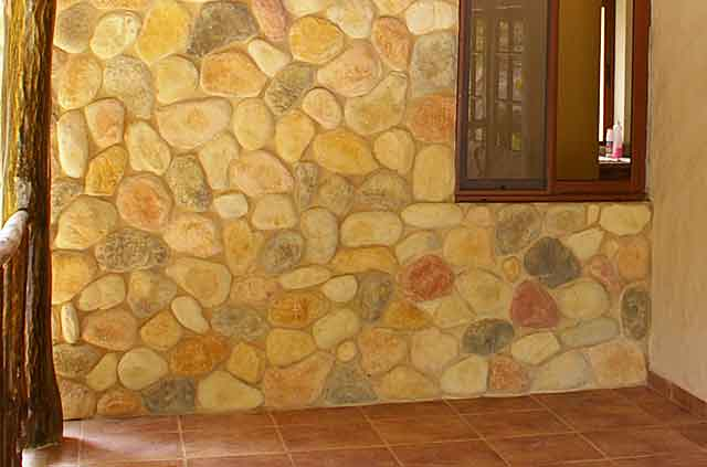 Photo example of a wall on country house built with beige and redish river stones. Real or Fake?