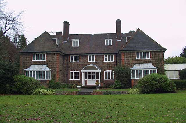 Photo of a big traditional house with a huge garden near London, as many houses here this one shows the natural brick walls exterior and white painted window and door frames