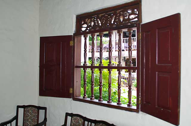 Photo example of an old colonial window without glass but with a decorative wooden frame