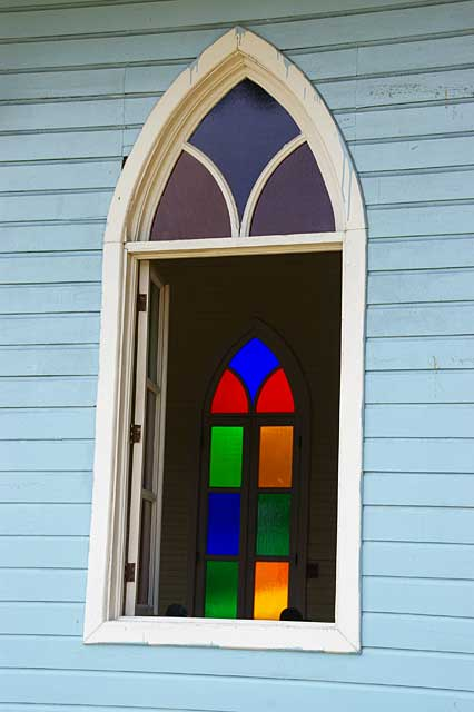 Photo example of an old church window with colored glass panels, this is a Caribbean style church