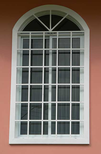 Photo example of a window with security metal square frames painted in white on salmon red walls